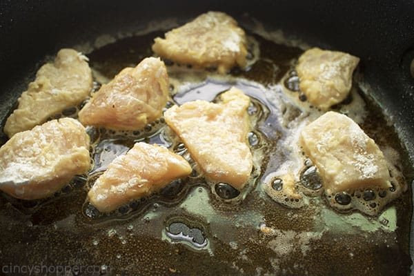 chicken frying in a dark pan