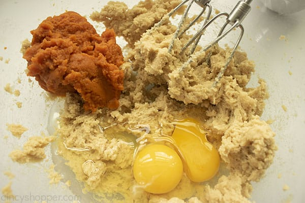 Eggs and pumpkin added to blended sugar mixture in a clear bowl with beaters