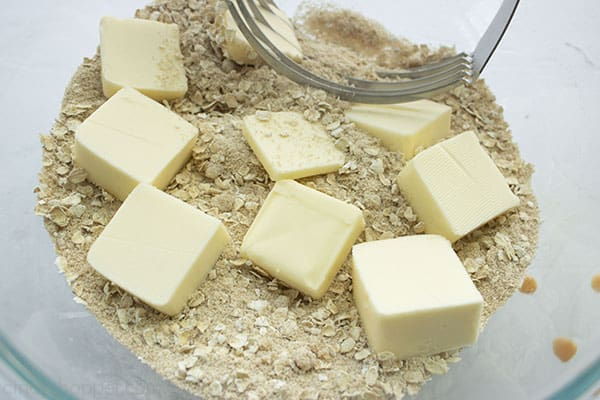 Butter added to crisp ingredients in a clear bowl with a pastry blender