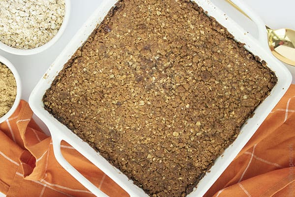 Horizontal image of baked crisp in a white dish with orange napkin, oats, brown sugar and gold spoon.