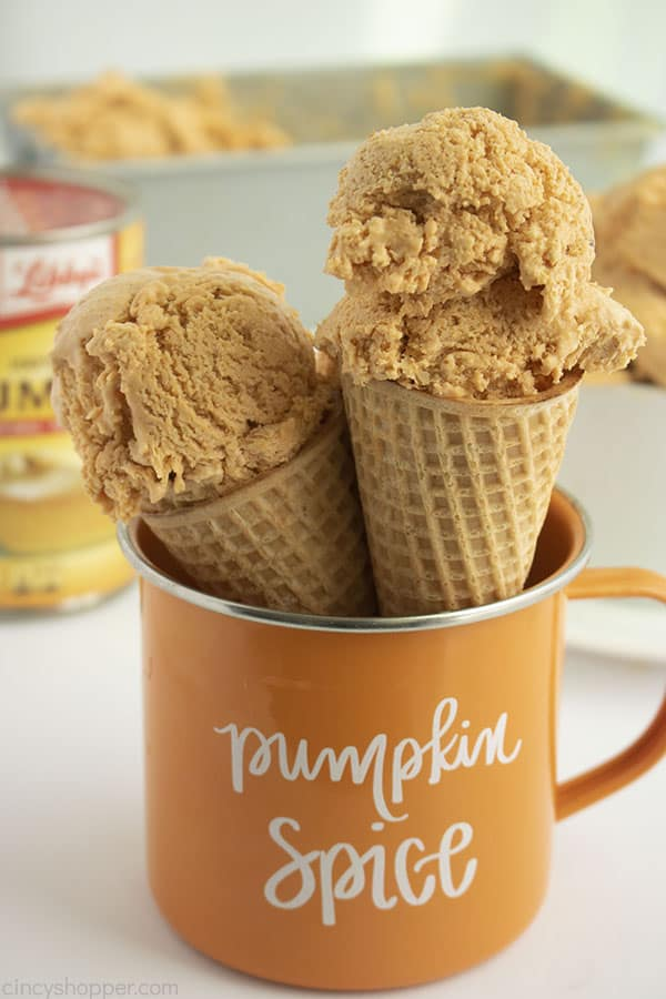 Two pumpkin ice cream cones in a orange mug with Pumpkin Spice text