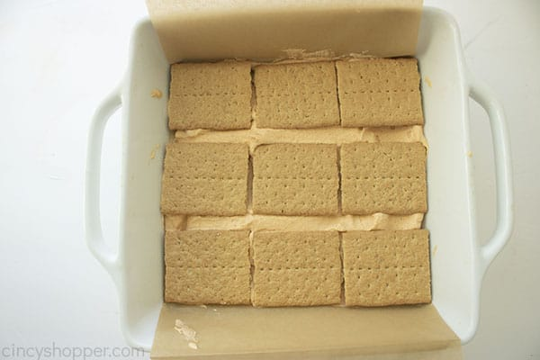 Overhead image of graham cracker layer being added to the top of the mixture