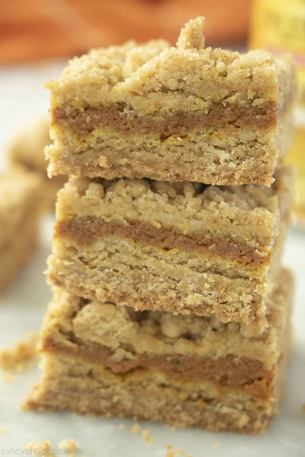 Stack of three Pumpkin Bars with orange napkin in the background