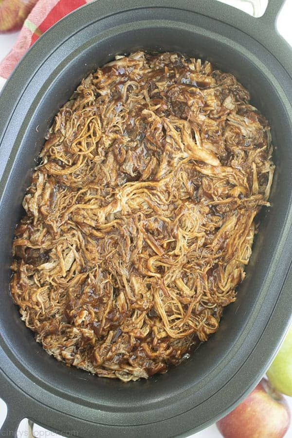 Overhead shot of Apple Cider Pulled Pork in the a black oval Slow Cooker