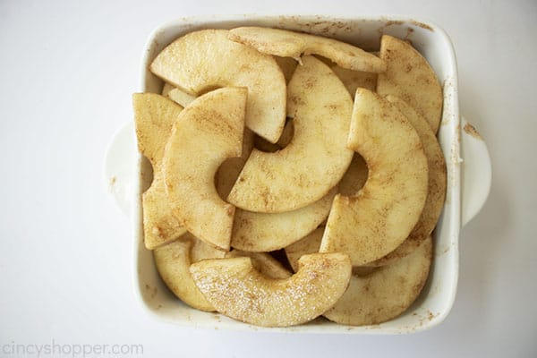 Sliced and coated apples in a small white baking dish