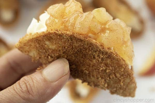 Hand holding finished dessert taco with apples