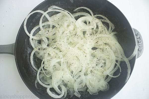 onions cooking in a dark pan.