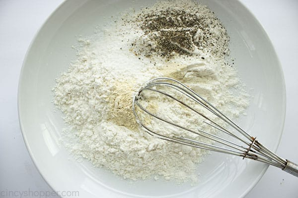 Flour and spices in a dish with whisk.