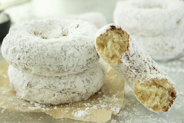 Two powdered donuts with leaning half donut