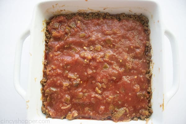 Picante sauce added to the top of ground beef layer