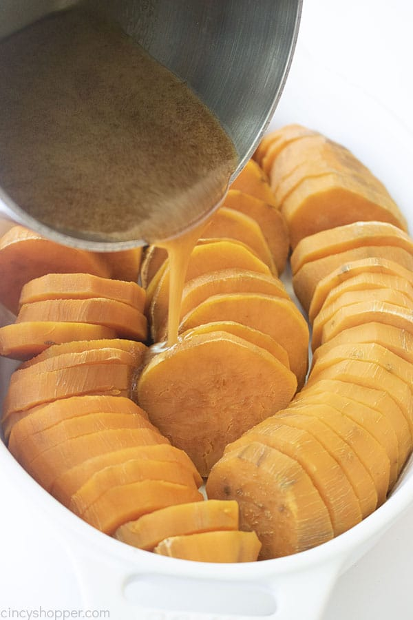 Sauce pouring on sliced potatoes