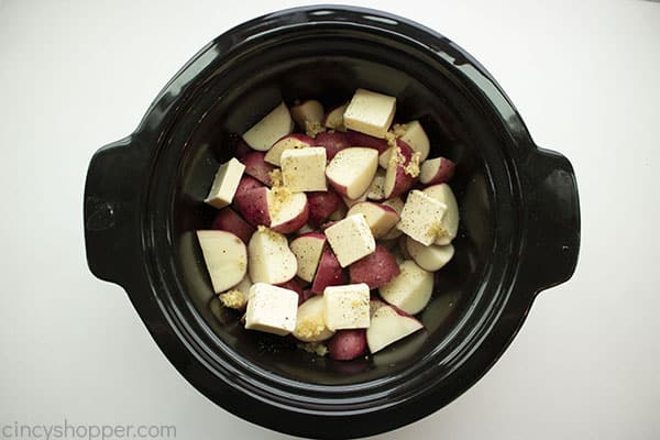 Potatoes, butter, minced garlic, and salt & pepper in slow cooker