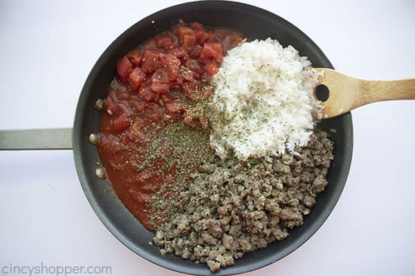 Spices, rice and tomatoes added to pan