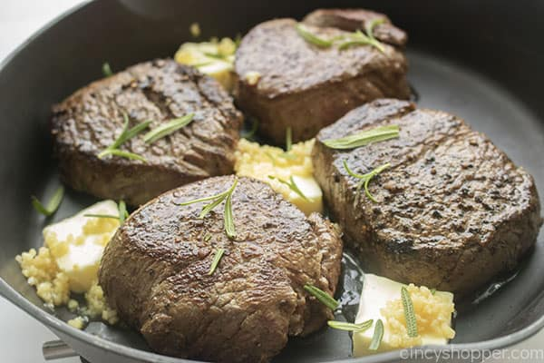 Pan seared filet mignon steaks in pan with butter, garlic and rosemary