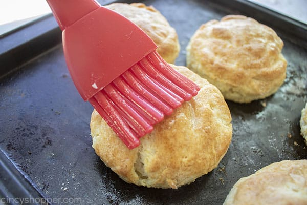 Buttering the tops of homemade biscuit