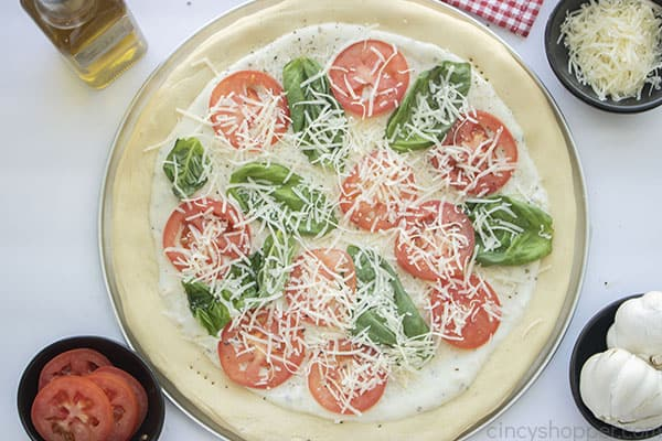 White sauce on pizza dough, basil and tomatoes added
