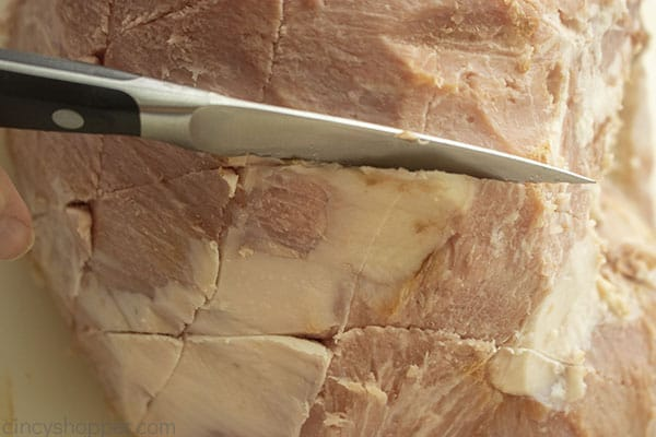 Slicing whole ham with diamond pattern
