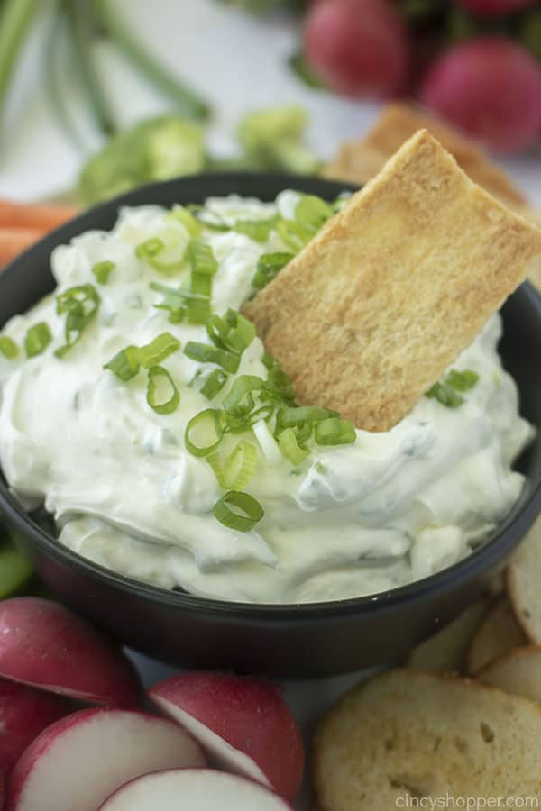 Pita chip dipping in homemade onion chip dip