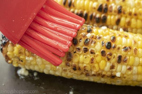 Brushing garlic butter onto corn on the cob