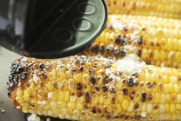Adding parmesan cheese to grilled corn