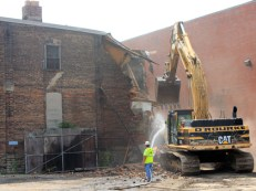 With one swipe, demolition was underway at Henry and Race streets...