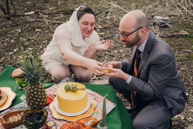 wedding couple eating yellow cake outside