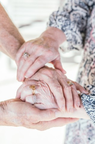husband and wife grandparents clasping hands with rings