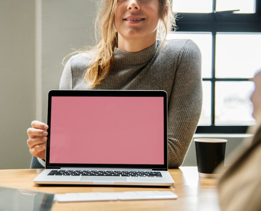 woman pointing at a pink laptop screen