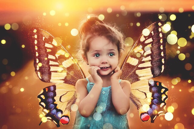 Three year old girl with butterfly wings.