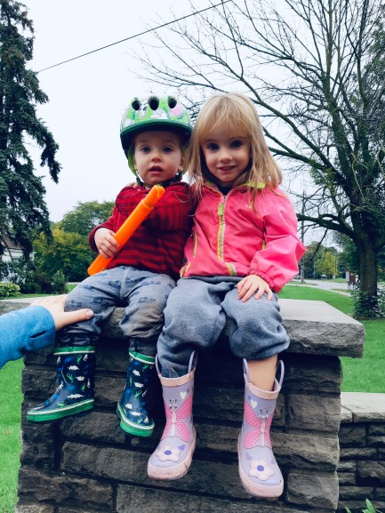 Katy's two kids sitting on top of a brick wall.