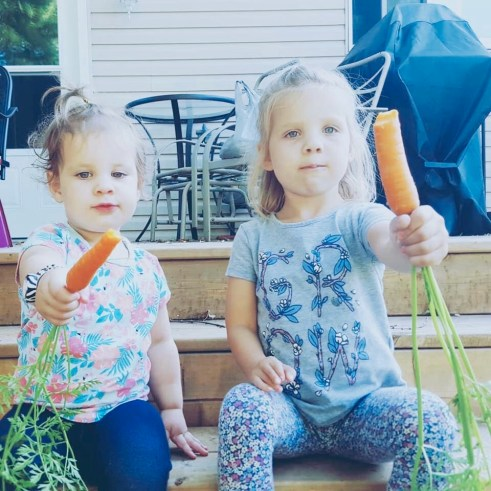 Cherie's daughters sitting on outdoor deck eating carrots.