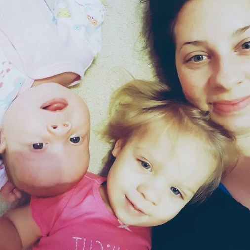 Cherie and her two daughters laying on floor looking up at camera.