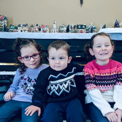 The three kids sitting in front of the piano in winter sweaters