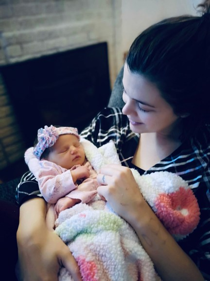 A young mother holding her newborn daughter in front of a fireplace.