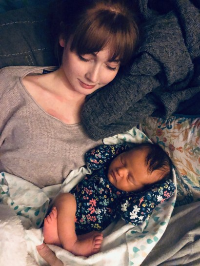A young woman in a pink sweater, looking down at a sleeping baby wearing a floral sleeper. .