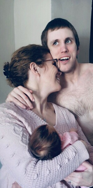 Thirty-year-old man huggling his mom as she holds her newborn granddaughter,