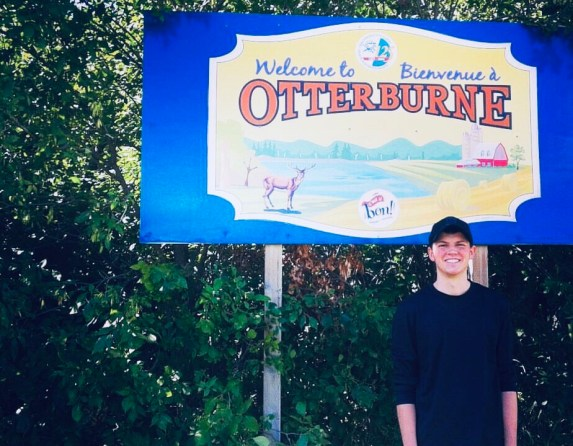 """A young man standing in front of a sign that says, """"Welcome to Otterburne."""""""