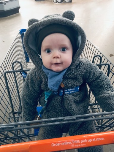 A baby boy sitting in the front of a grocery cart.