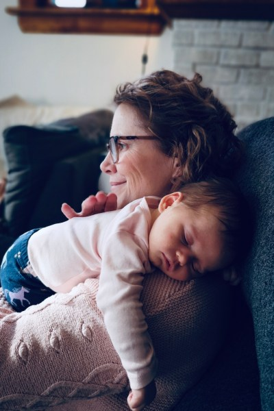 Grandmother holding sleeping baby over her shoulder. Baby is wearing pink. Grandmother is smiling.