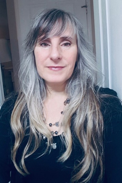 a portrait of a woman with long grey hair. She is wearing a black sweater and a beaded necklace.