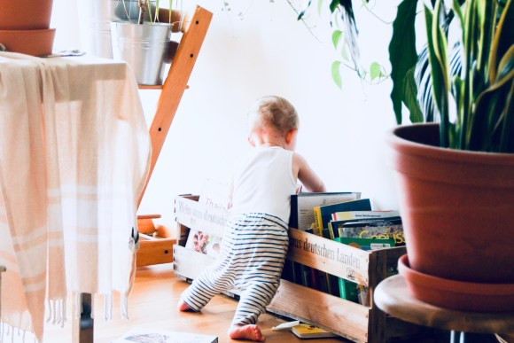 baby sorting through a box of books