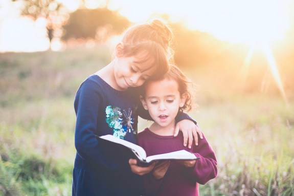 two little girls reading a book outside together.