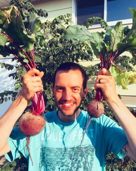 Dave holding two bunches of beets and smiling.