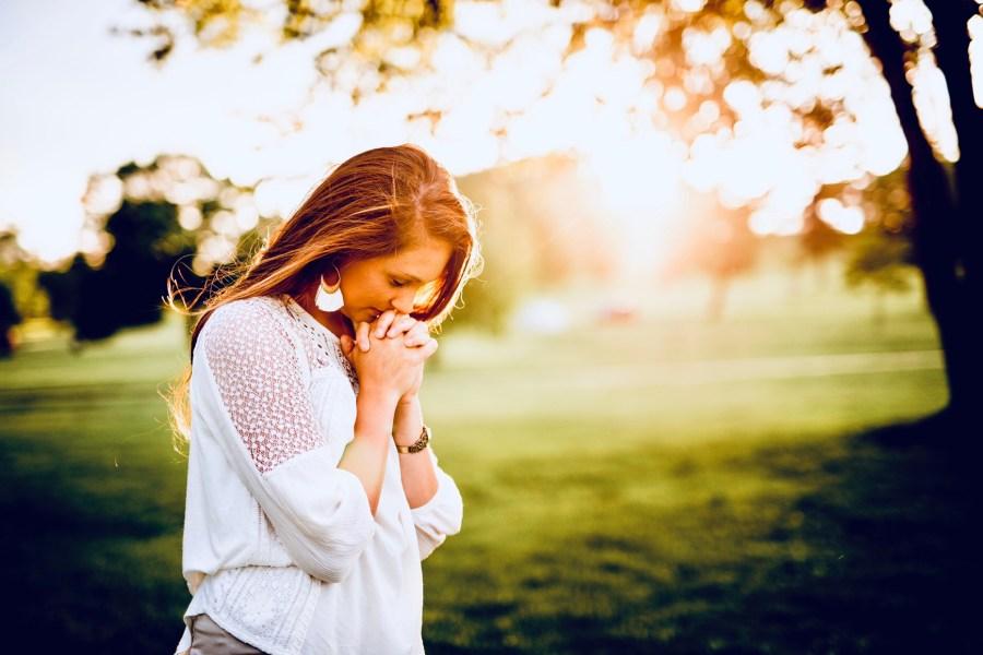 A woman praying near a field