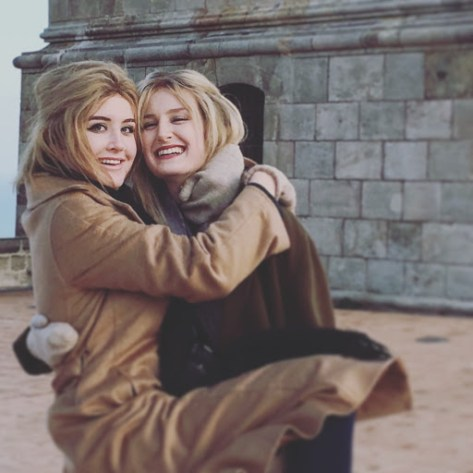 Gayle and Jillian in warm coats, hugging and smiling