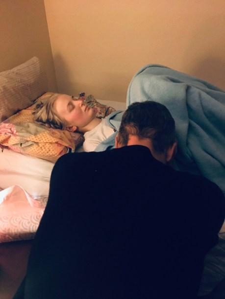 Jason praying beside Gayle's bed.