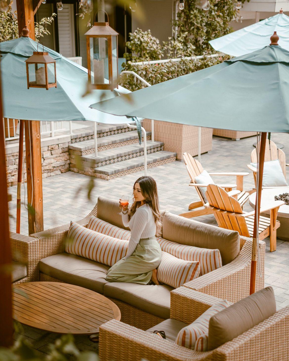 girl enjoying a mimosa in dreamy courtyard, Hotel Carmel