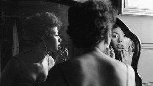 Archival photo of woman applying lipstick in the mirror. We see the woman's back and two different reflections.