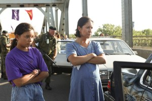 A woman and young girl both cross their arms looking at a car. A military person is in the background.