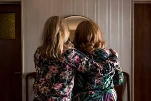 Two women with blonde hair face away towards a mirror. Both are wearing jackets with pink flowers.